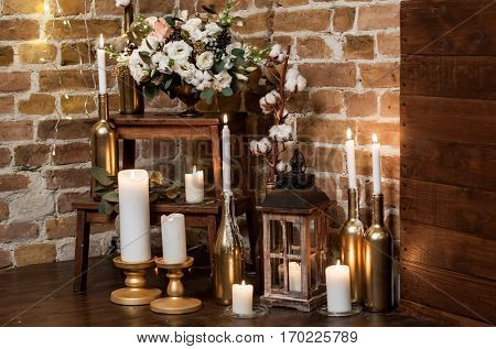 Many burning candles on candlesticks and lantern with fresh flower arrangement