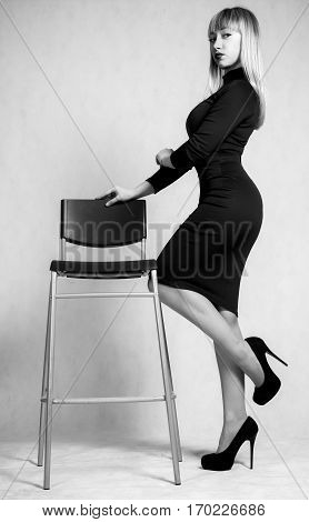 Beautiful Young Woman In A Short Dress Staying Near The High Chair