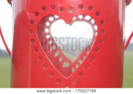 Round perforations in the form of a heart on red lacquer metal, in the background further round perforations in the form of a heart on red lacquer metal with bright daylight through which one can see in the background, meadow, forest and sky, In the sun i