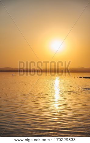 View of the salt lake with a beautiful pink water. Sunset orange sun, the neighborhood.Las salinas, Torrevieja, Spain,