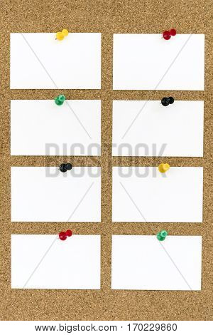 Eight blank business cards with push pins on cork board.