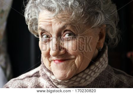 Smile grandmother face on a dark background