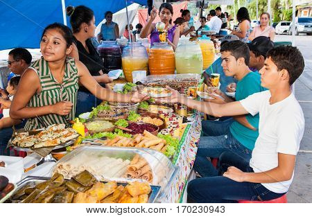 FLORES, GUATEMALA-DEC 20, 2015:  Local women sell a typical Guatemalan food plate in Flores on Dec 20, 2015. Guatemala.