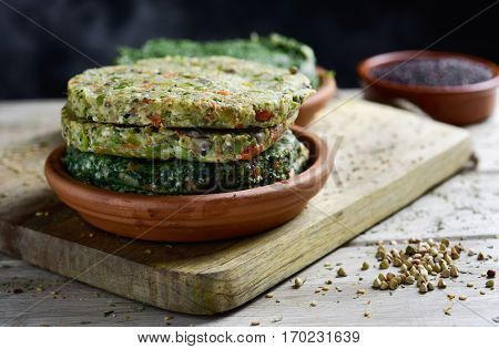 closeup of some different raw veggie burgers in an earthenware plate, on a rustic wooden table
