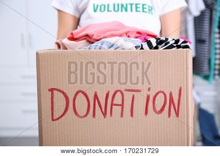 Female volunteer holding donation box with clothing
