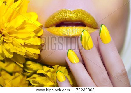 Yellow manicure and makeup on a woman with flowers closeup.