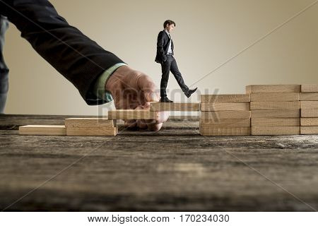 Businessman in business suit walking up steps while the hand of other man helping him in a conceptual image of insurance assistance and support.