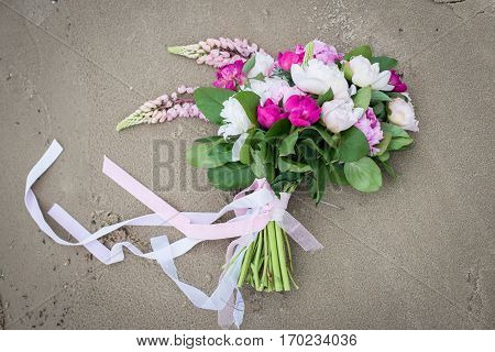 Delicate bridal bouquet with white and pink peony and greenery with long ribbon lying on wet sand on the bank of river
