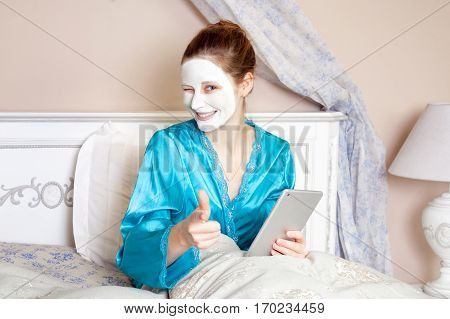 Beautiful woman with green nightie and white facial mask resting on bed and holding tablet before sleeping. healthcare and beauty treatment and technology concept. studio shot.