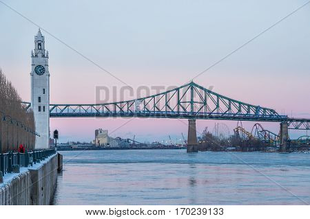 Montreal CA - 5 February 2017: Montreal Clock Tower and Jacques Cartier Bridge in Winter after sunset