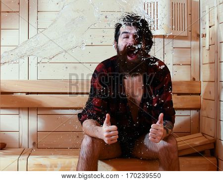 Excited man or bather bearded hipster with beard and moustache in red checkered shirt wet with big splash of water gives thumbs up gesture in sauna thermal bath on wooden background
