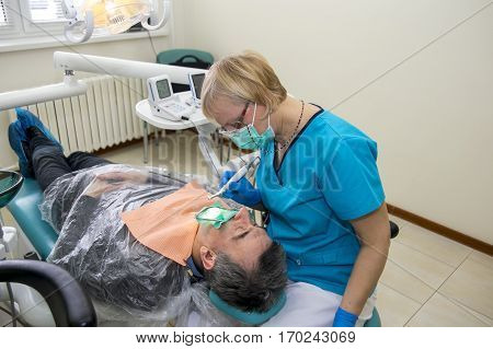 GRODNO BELARUS - FEBRUARY 8: GRODNO BELARUS - FEBRUARY 8: Professional dentist determined rehabilitation of the oral cavity to remove pockets of infection in men 8 February 2017 Grodno Belarus