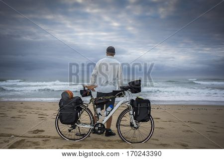 Long Distance Cyclist On Beach With Bicycle