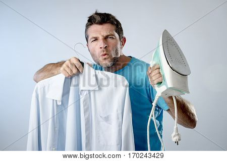 young attractive and satisfied man holding iron and slick shirt smiling happy and cocky in male ironing good style and domestic work concept isolated even background