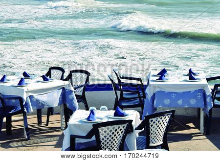 Relaxing lunch. Tables prepared for lunch by the sea.
