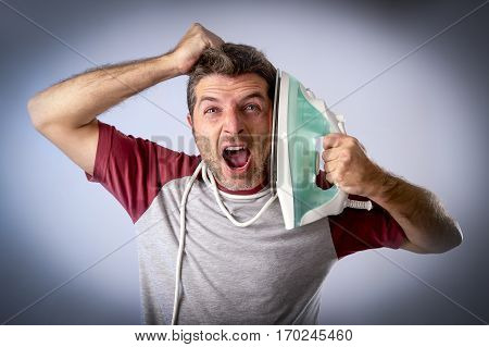 young crazy desperate and frustrated man doing housework holding iron against his face and cable stressed and confused in unskilled and unable male for ironing isolated on even background