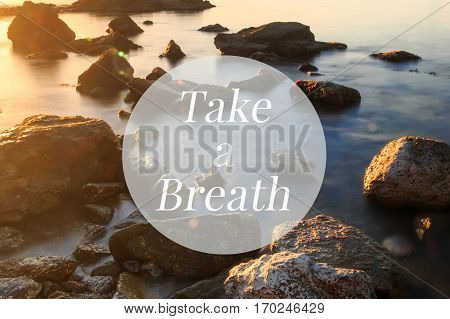 Inspirational motivation quote, take a breath, on a sea shore in sunset background