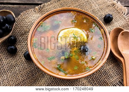 Meat soup with black olives on a wooden background with wooden spoon and sack