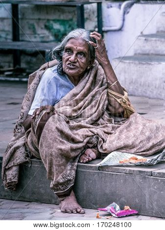 Madurai India - October 19 2013: An old graying lady sits on the sidewalk of the street around Meenakshi Temple. She has an expressive dismissing face scratches her hair and wears a brownish sari.