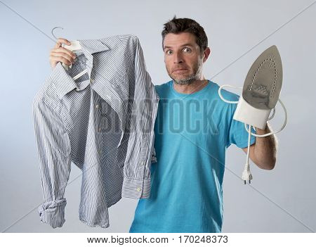 young attractive and frustrated man holding iron and shirt stressed and tired in bored and lazy face expression in male ironing going wrong and domestic work concept isolated even background