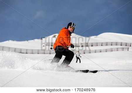 Male skier wearing a modern colourful orange ski jacket skiing down a ski slope.