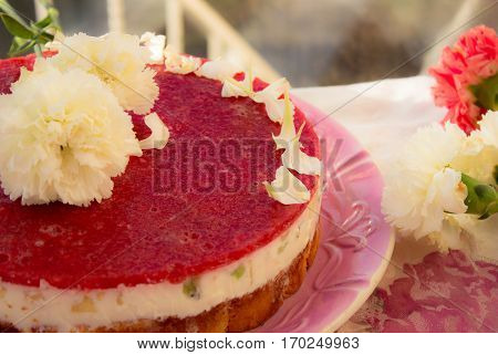 Closeup of a strawberry cake from side on white batskground sponge cake with jelly and fruit on the background of the railing. decorated with white flowers