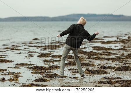 Blond Boy On Beach Throwing A Rock
