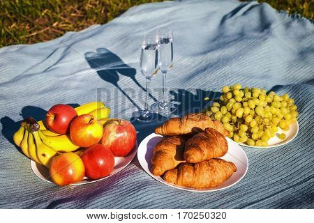 Still life with croissants, apples, grapes, bananas and wine. Healthy lifestyle concept. Useful and tasty breakfast
