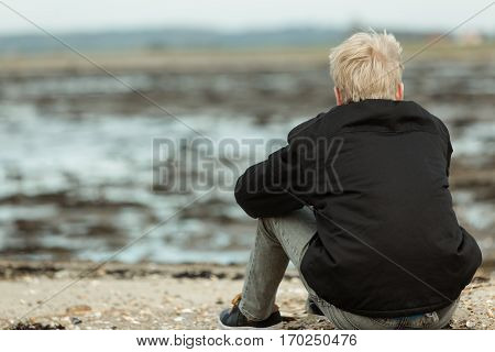 Rear View Of Blond Person Sitting On Rocky Beach