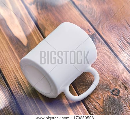 White cup laying in the center of wooden table