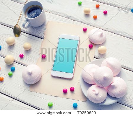 Template of smartphone among colour sweets on the table. Clipping path