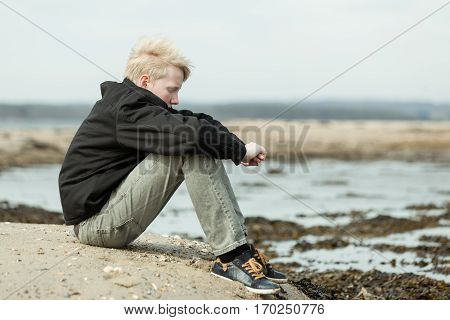 Lonely Child With Arms Around Knees Outside