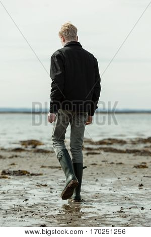 Young Man Walking Alone On Beach