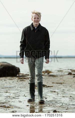 Young Man In Boots And Jacket Walking On Beach