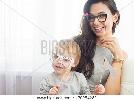 Funny family. Mother and her child daughter girl with a paper accessories. Beautiful young woman and her funny girl holding paper glasses on stick.