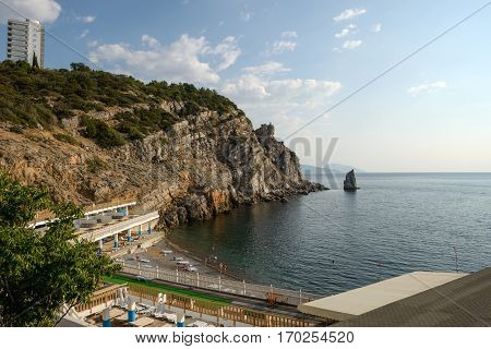 GASPRA, CRIMEA, RUSSIA - AUGUST 31: Sun of summer morning is illuminating beach of Ai-Todor bay and vacationers on it under cliff of Sail sanatorium on August 31, 2016 in Gaspra, Big Yalta area, Crimea, Russia.