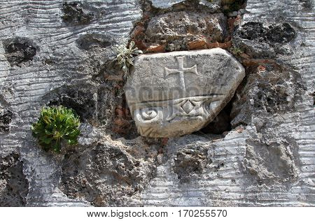 Ancient cross on the wall of ruined Greek Orthodox Church in the Ghost town of Kayakoy (Turkey)