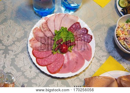 Plate of cold sliced meat on the table - the view from the top. Table ham and bacon. Festive food and refreshments served. Gluttony and gluttony is human. Consumption of food in large quantity.