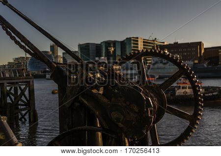 old rusty parts of the coastal crane on the banks of the river in London gears and chains in the background buildings canal and boat