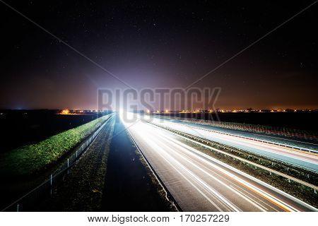 highway at night starry sky. light vehicles