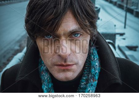 Middle-aged man in a blue scarf and a greenish coat. Man with beautiful big blue eyes