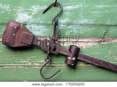 Vintage steelyard on a wooden background closeup