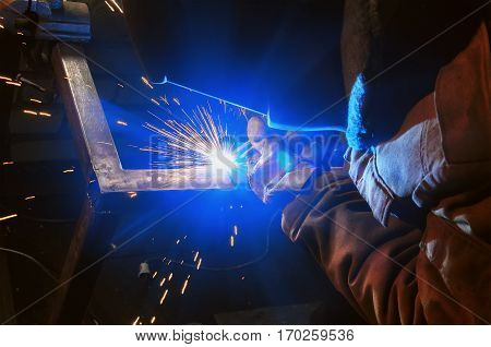 welder in a protective mask in a dark shop floor weld metal parts. By welding sparks fly in different directions