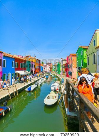 Burano, Venice, Italy - May 10, 2014: The people walking at street with colorful old houses on the Island of Burano near Venice, Italy on May 10, 2014