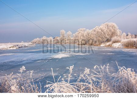Winter river nature.landscape in early winter morning- deciduous frosty grass under snowfall and warm sunlight - blue sky. Beautiful winter landscape.