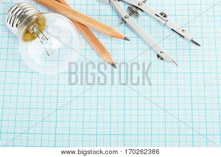 light bulb pencils and compasses on millimeter paper