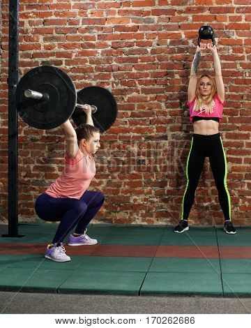 Two women are doing cross fit workout at the gym, one is lifting a barbell, the second is lifting a kettlebell against red brick wall