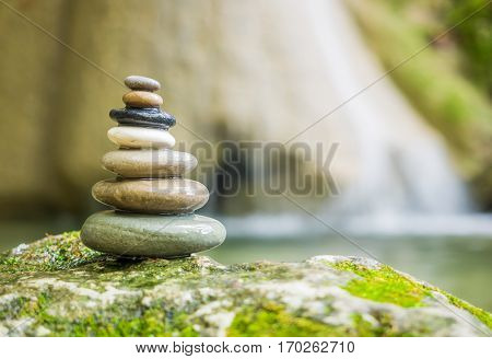 Balanced Rock Zen Stack in front of waterfall.
