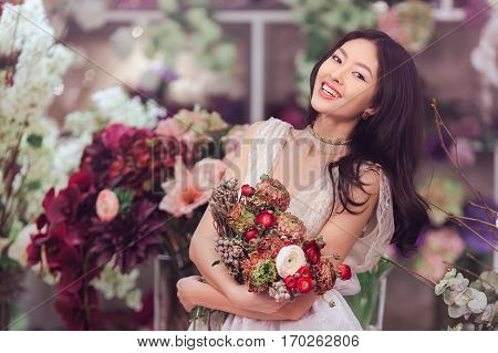 Beautiful girl in tender lacy dress with bouquet flowers peonies in hands standing against floral background in flower shop. Joyful asian female florist. Playful fashion model looking at camera and smiling.