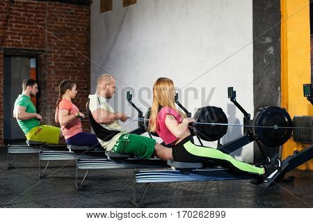 Young athletic people are doing workout on the rowing machines at the gym